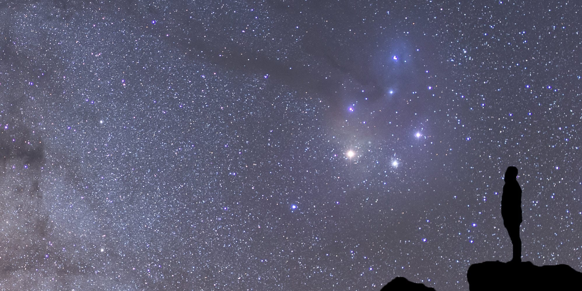 Silhouette of man gazing up at stars